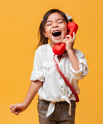 Excited girl talking on toy telephone